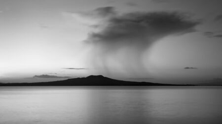 Black and white image of Milford beach with drifting dark rain clouds