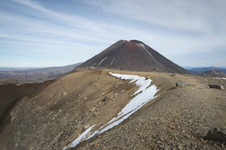 View of Mount Ngauruhoe in the distance with one person on the track on the Tongariro Alpine Crossing