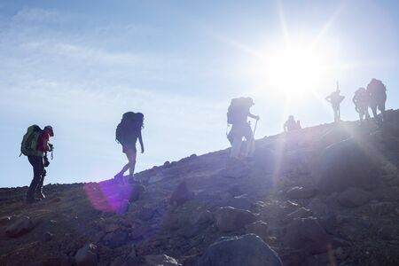 People hiking up the Red Crater with the sunrays shining on the Tongariro Alpine Crossing in New Zealand. Imagens