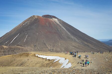 Tourists walking on the Tongariro Alpine Crossing with Mount Ngauruhoe in the background Imagens