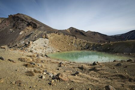 Looking up at the Red Crater from the frozen Emerald lake on the Tongariro Alpine Crossing