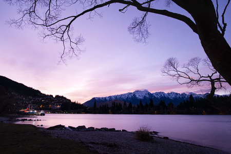 Lake Wakatipu and the Remarkables framed by winter willow trees at sunrise, Queenstown, New Zealand