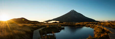 Panoramic image of Mt Taranaki reflected in Pouakai tarn at sunrise Imagens