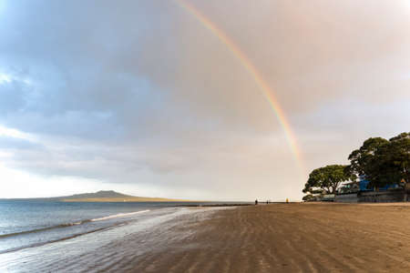 Rainbows at Milford beach with Rangitoto Island in the distance