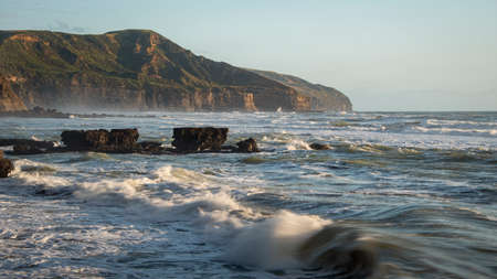 Cliffs and rocks of Muriwai in late afternoon, Auckland. Image taken using slow shutter speed to capture the blurred movements of the waves.