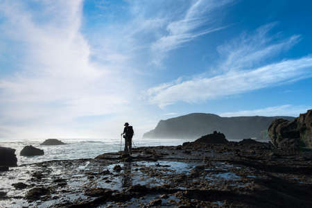 A backpacker standing on the rocks at Anawhata beach, Waitakere, Auckland