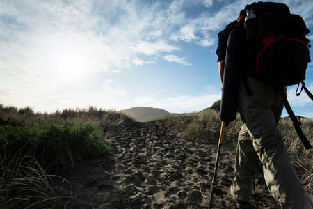 A backpacker walking on the sand track towards the Anawhata beach, Auckland