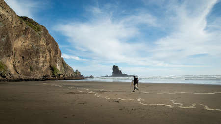 A backpacker walking on the black-sand Anawhata beach with keyhole rock in the distance, Waitakere, Auckland