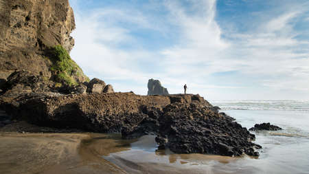 A backpacker looking at the keyhole rocks at Anawhata beach, Waitakere, Auckland Imagens