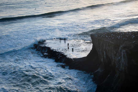 People fishing on the big rock of Muriwai gannet colony with big waves crashing against the rock