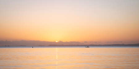 Sun rising over the clouds, a tiny boat paddling in the pastel coloured ocean