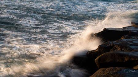 Crashing waves against the rocks at sunset