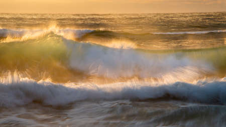 Crashing waves back lit by the setting sun. Image taken using slow shutter speed to capture the movement of the waves. Imagens