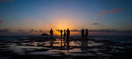 Silhouette image of people enjoying sunset at Muriwai beach, Waitakere, Auckland