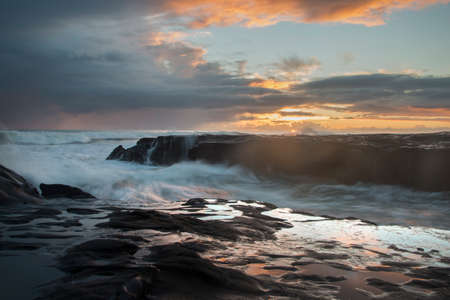 Sunset at Muriwai beach with splashing waves against the rocks