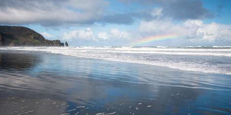 Panorama image of rainbows at Piha beach, Waitakere, Auckland