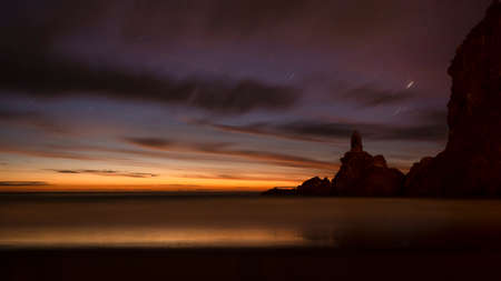 Piha beach at dusk with star trails and last sunset colours Imagens