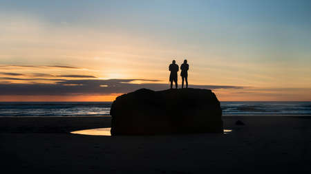 Silhouette image of two people standing on big rock and watching sunset at Muriwai beach, Waitakere, Auckland Imagens