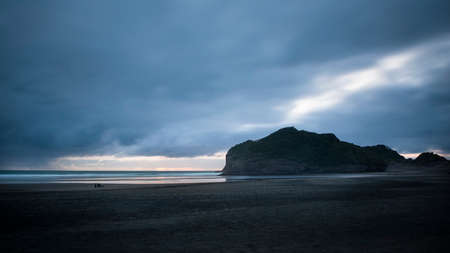 Sunset at Bethells beach with stormy dark clouds, Waitakere, Auckland Imagens
