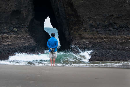 A young man standing in front of the keyhole rock on Piha beach with waves crashing under his feet