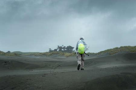 Man walking in the strong wind and heavy rain at Wharariki Beach, South Island, New Zealand