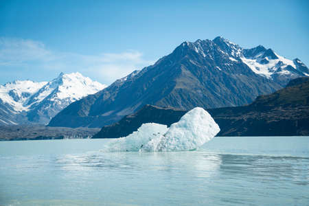 Icebergs floating in the Tasman Glacier terminal lake with snow-capped mountains in the background, Mt Cook National Park