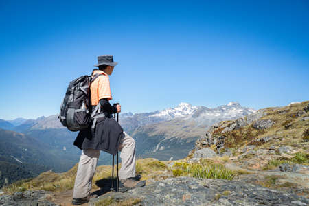 A backpacker enjoying panorama views of the mountain ranges on day 2 of the Routeburn Track, South Island.