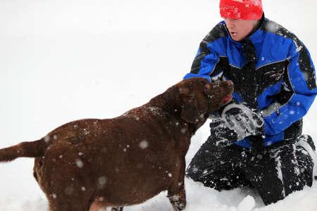Fun in the snow - Boy and dog having  fun 写真素材