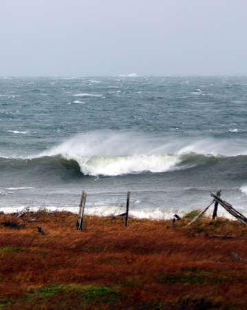 wzburzone morze: Stary płot i szorstkie morze z falami tocznych w Zdjęcie Seryjne