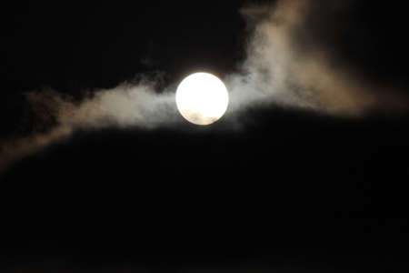 glows: Full moon peeking out behind the clouds