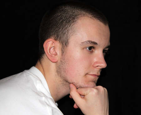 Serious Looking Young Man Resting Chin on Hand photo
