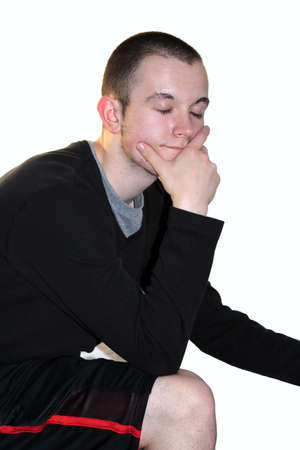 Teenage boy posing with elbow resting on knee and eyes closed