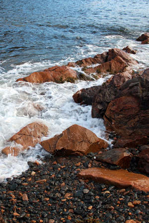 Small waves, large rocks, pebbles and kelp Stock Photo
