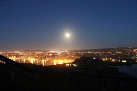 City at dawn - the moon going down in the west as the sun comes up in the east photo