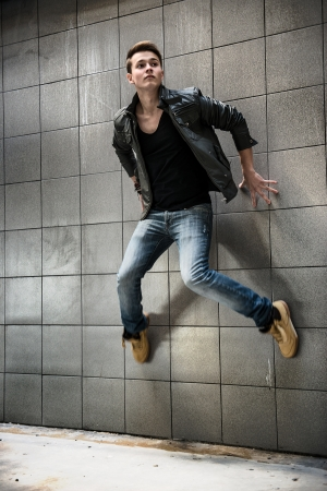 fashion photo of handsome man jumping on the street wall