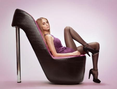 Beautiful young woman sitting on a trendy shoes photo