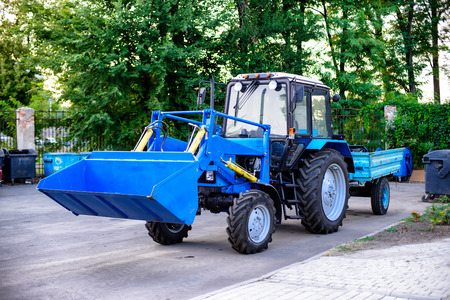 Blue tractor with trailer for cleaning park territories in the city