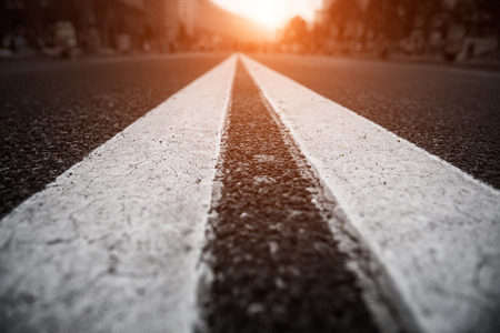 tar: Asphalt city road with white lines ahead and the sunset Stock Photo