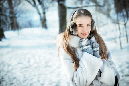 muff: Happy beautiful woman walking in earmuff, knitted mittens and fur coat have fun in winter forest Stock Photo