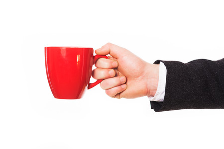 Concept photo of business coffee break. Man holding red coffee mug isolated on white.