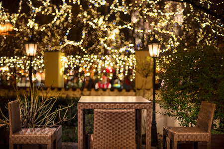 patio chair: Street cafe at the night agains city illumination lights Stock Photo