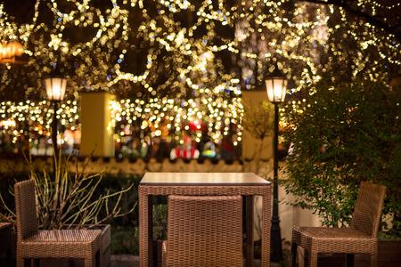 Street cafe at the night agains city illumination lights Фото со стока