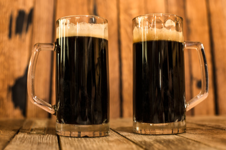 Two glass of fresh dark beer on wooden table photo