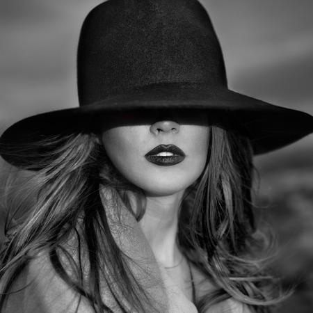 l  ¡piz labial: Retrato monocrom�tico de la mujer elegante y bella mujer llevaba un sombrero Foto de archivo
