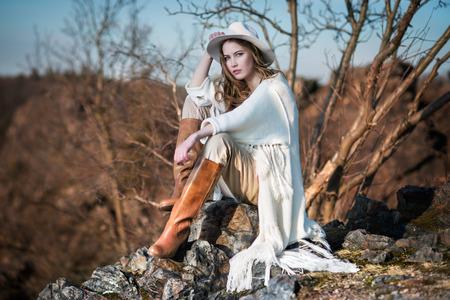 mujeres fashion: Mujer de la manera en estilo r�stico sentado en la roca del ca��n Foto de archivo