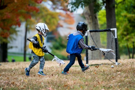 Active little kids playing lacrosse in the park