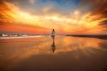 lejos: mujer caminando en la playa cerca del océano en la puesta del sol