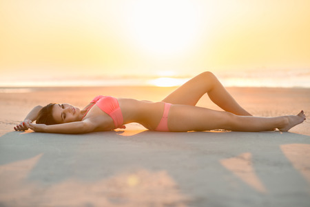 beautiful woman with perfect body lying on the beach