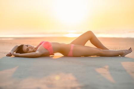 nias en bikini: hermosa mujer con cuerpo perfecto que miente en la playa Foto de archivo