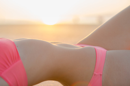 nude sexy woman: Beautiful woman body in swimsuit on the beach at sunset time Stock Photo